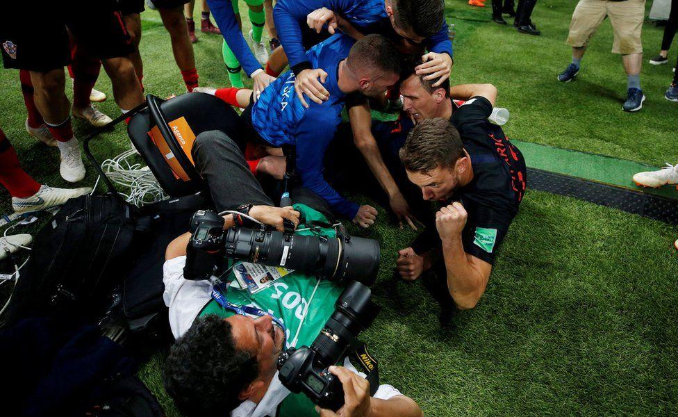 Croatia players celebrate next to an AFP photographer Yuri Cortez