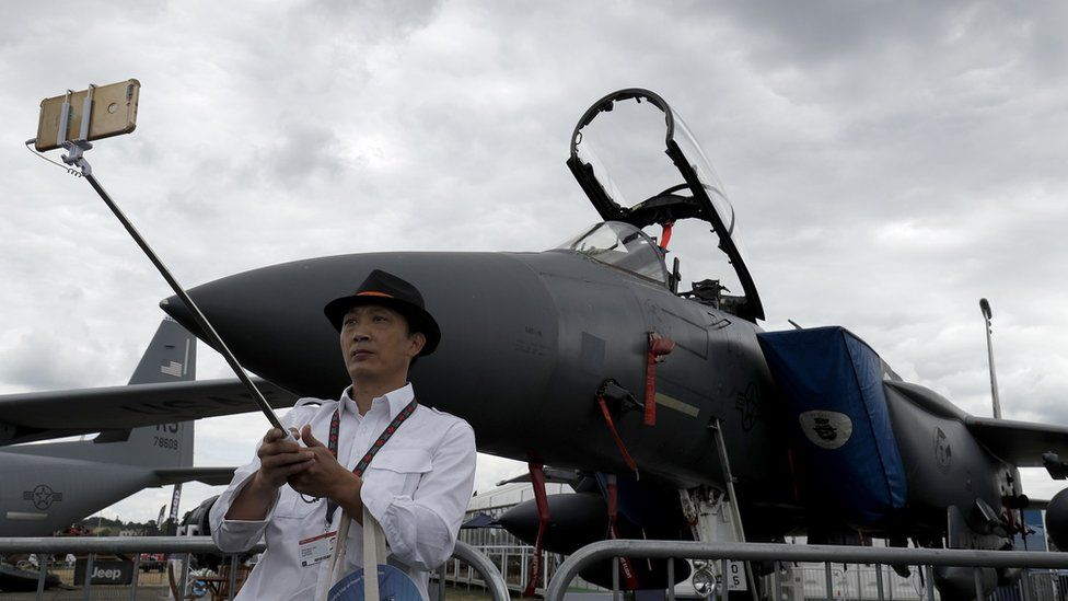 A visitor takes a selfie photograph in front of a Boeing F15E fighter aircraft