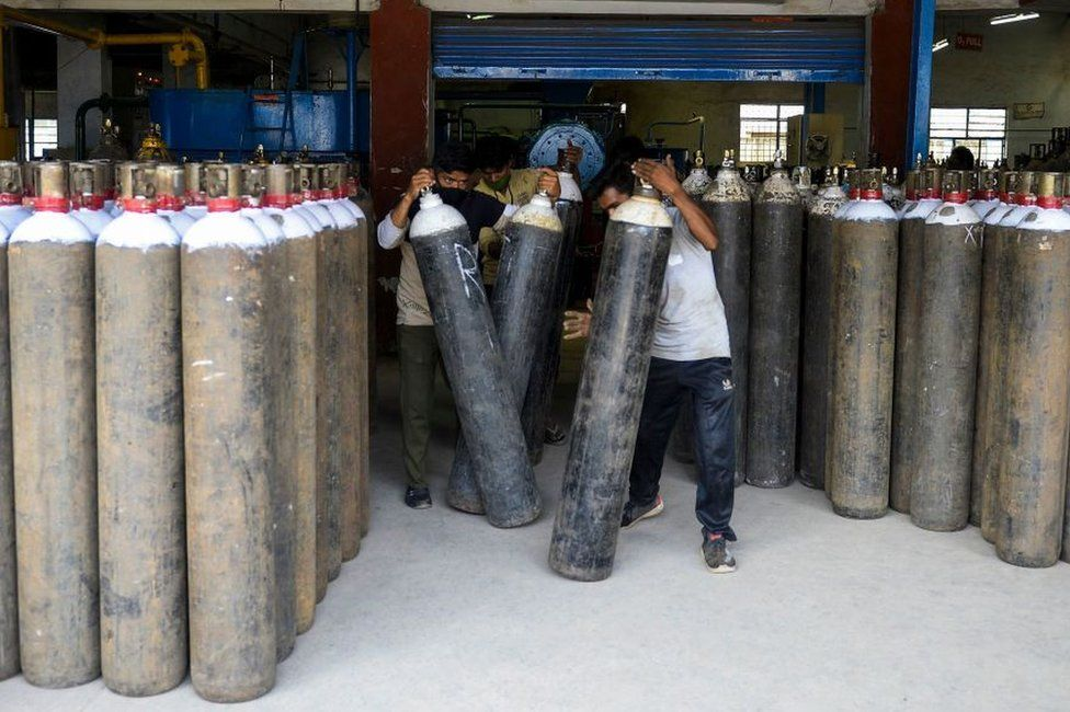 Workers arrange medical oxygen cylinders to transport to hospitals for the Covid-19 coronavirus treatment in a facility on the outskirts of Hyderabad on April 23, 2021.
