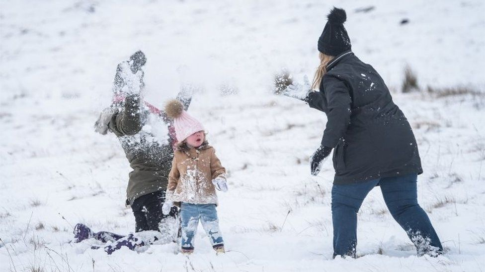 Families having snowball fights on the mountains at Brecon Beacons National Park, Wales