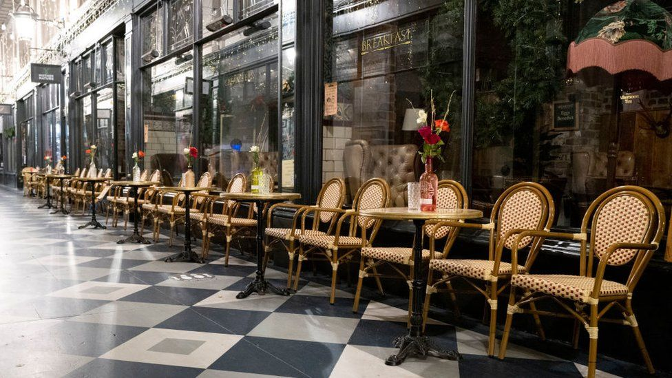 High Street Arcade in Cardiff with empty chairs outside a tearoom