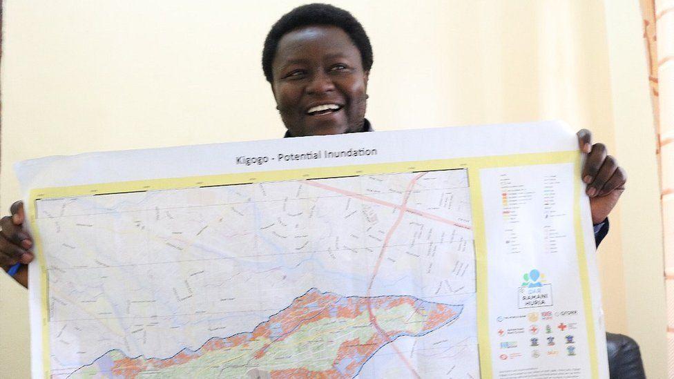 Osiligi Losai holds up one of the drone maps