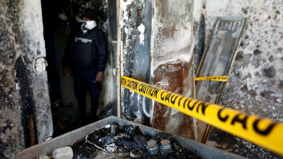 A police officer looks at burnt debris at an orphanage after it was partially destroyed in a fire, in Port-au-Prince, Haiti, 14 February, 2020