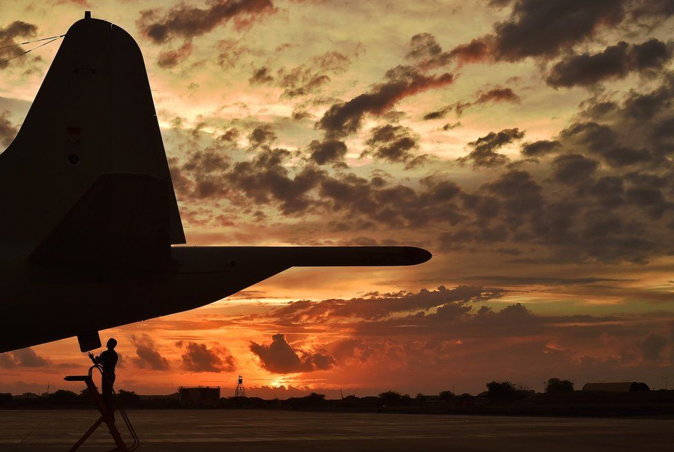 An airman makes technical checks to an anti-piracy reconnaissance plane at sunset in Djibouti