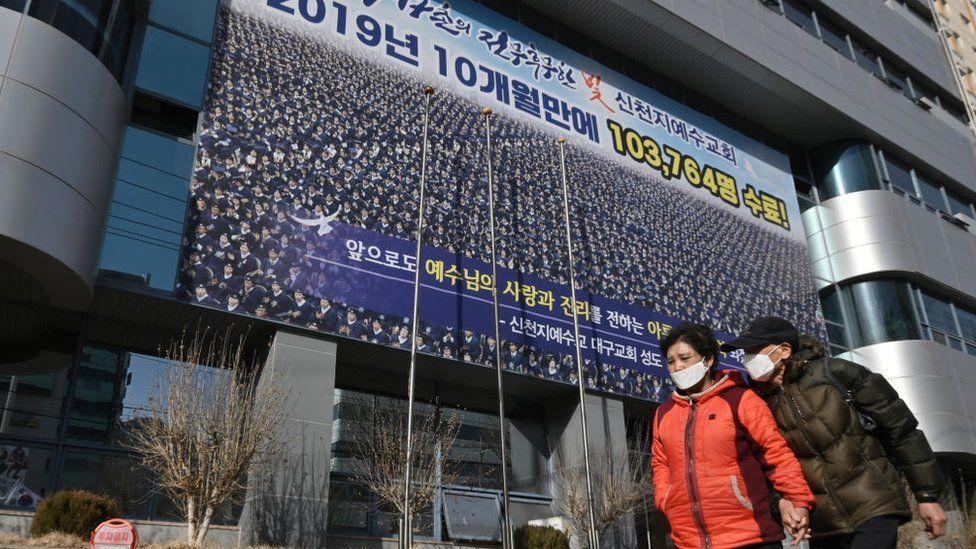 Pedestrians wearing face masks walk in front of the Daegu branch of the Shincheonji Church