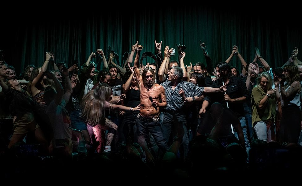 Music artist Iggy Pop dances on stage with fans