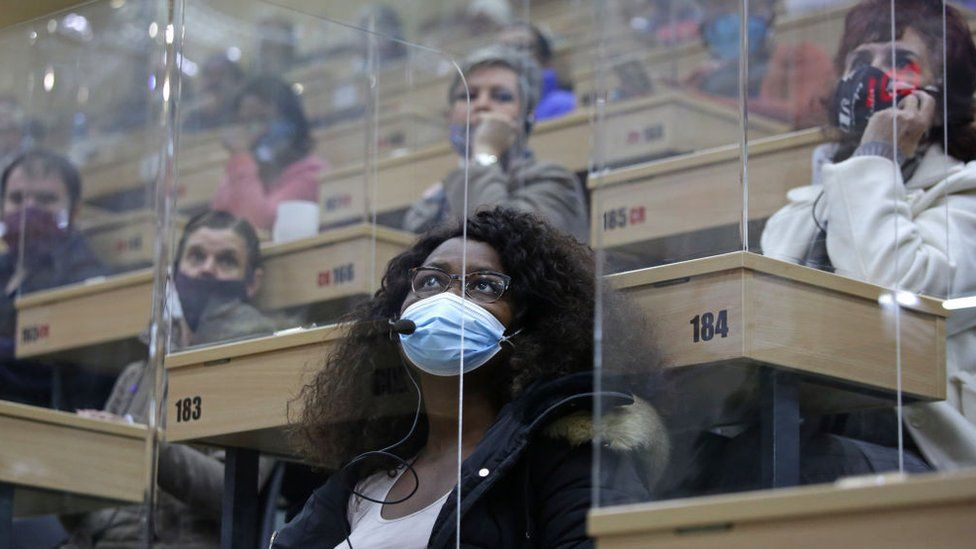 People sitting in separate perspex cubicles react as they bid for flowers during an action inside the Multiflora warehouse in Johannesburg, on May 8, 2020. - Multiflora is a specialised flower auction space where some 300 million flower stems are auctioned and sold into the flower market in South Africa.