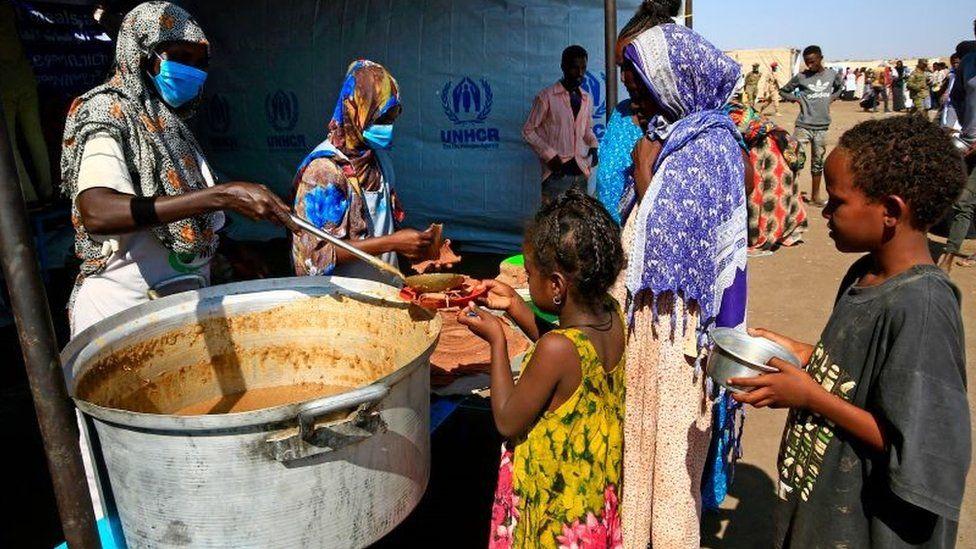 Les réfugiés éthiopiens qui ont fui le conflit du Tigré reçoivent de la nourriture dans un centre de transit de la ville frontalière soudanaise de Hamdayit le 27 novembre 2020.