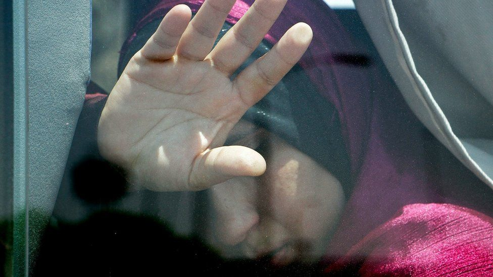 A relative of a passenger on an EgyptAir flight that crashed early Thursday puts her hand on the window from inside a bus at Cairo International Airport, Egypt, Thursday, May 19, 2016.