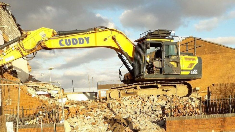 A digger knocking down a building