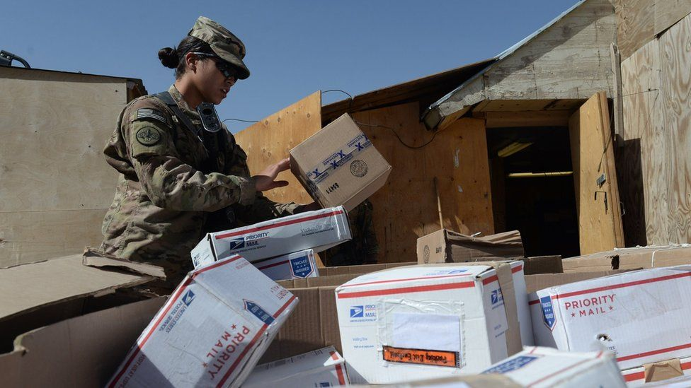 A US soldier sorts packages at a US base in Afghanistan, August 2014