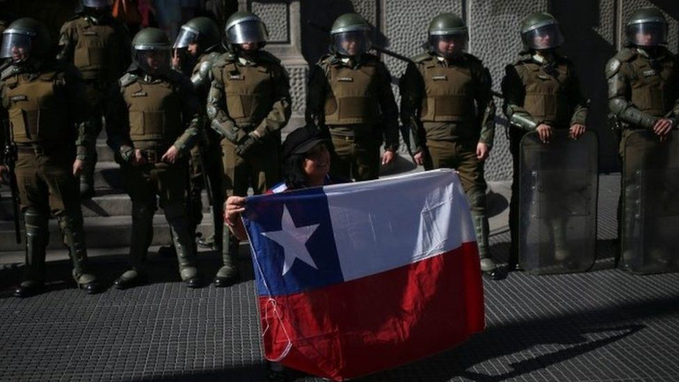 Protester holding Chilean flag ahead of police in Santiago