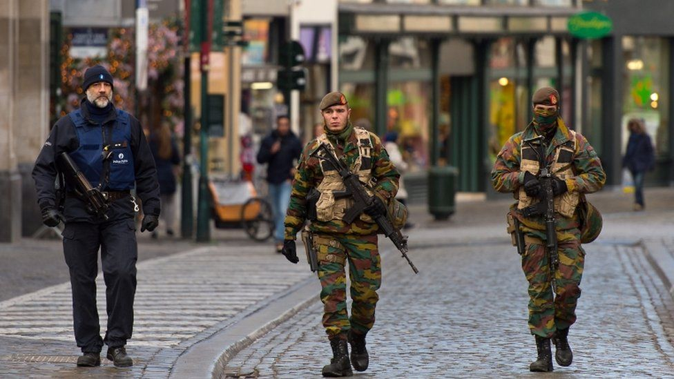 An armed policeman and two soldiers guard the shops on Rue Du Marche Aux Herbes on 23 November 2015 in Brussels