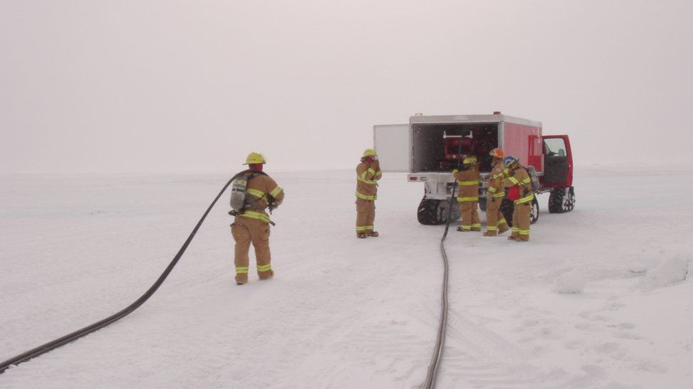 Five fire-fighters work from a vehicle parked on the ice. Hoses stretch behind them and the sky is white.