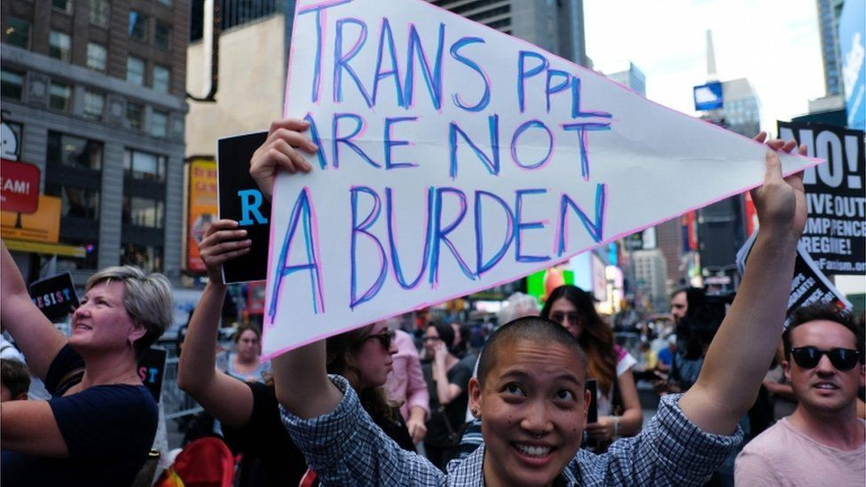 "a protestor holds a ""trans ppl are not a burden"" sign at a New York protest"
