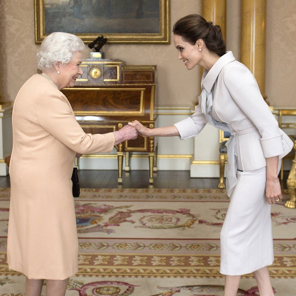 Actress Angelina Jolie being presented with the Insignia of an Honorary Dame Commander of the Most Distinguished Order of St Michael and St George by Queen Elizabeth II
