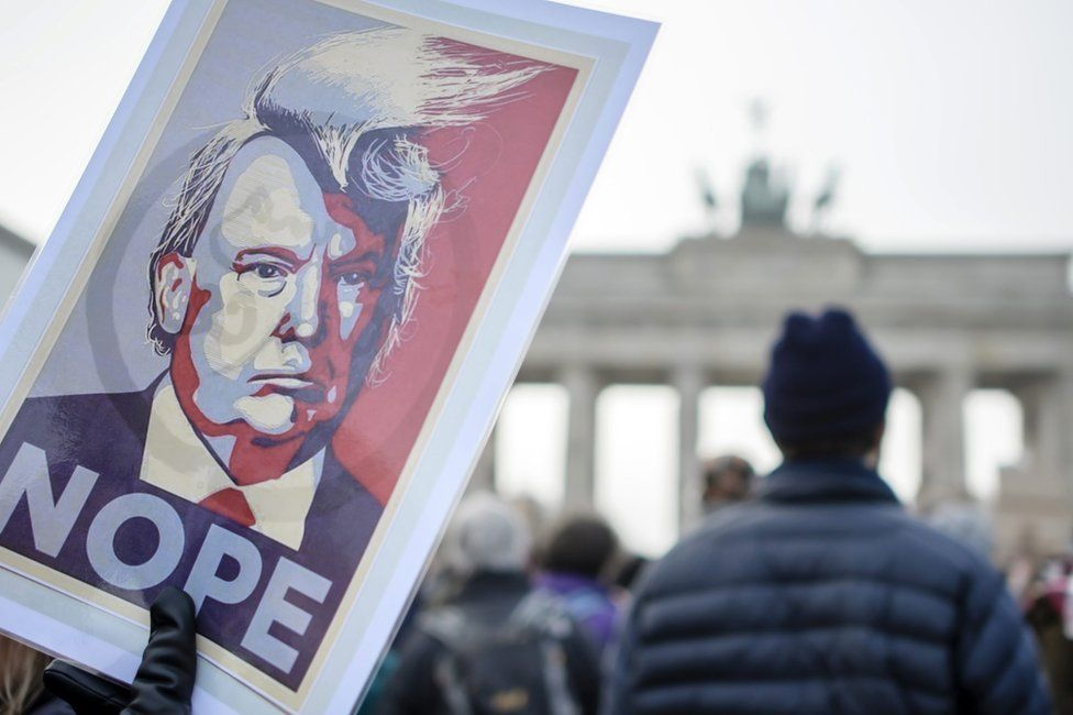 "A protester holds a poster with a portrait of Donald Trump reading ""Nope"" in front of the Brandenburg Gate in Berlin, Germany, 4 February"