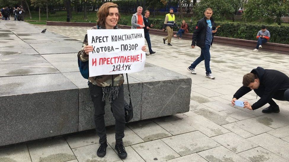 A protester holds a placard decrying an arrest as a disgrace on 17 August 2019