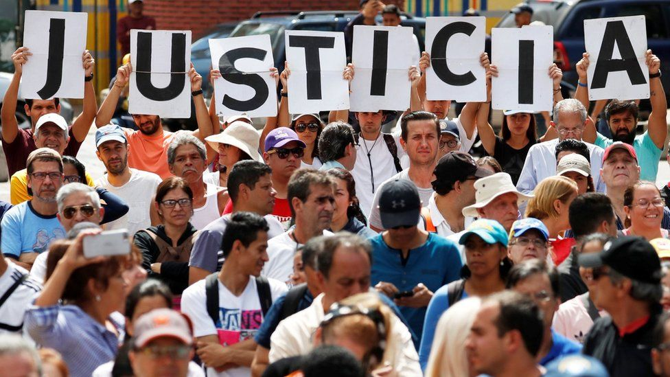 """Supporters of Venezuela's opposition leader Juan Guaido hold letters which read """"Justice"""" during a rally"""