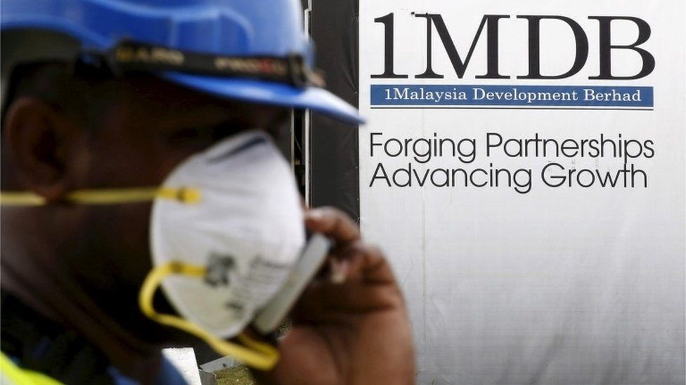 A construction worker walks past a 1MDB sign in KL, Malaysia