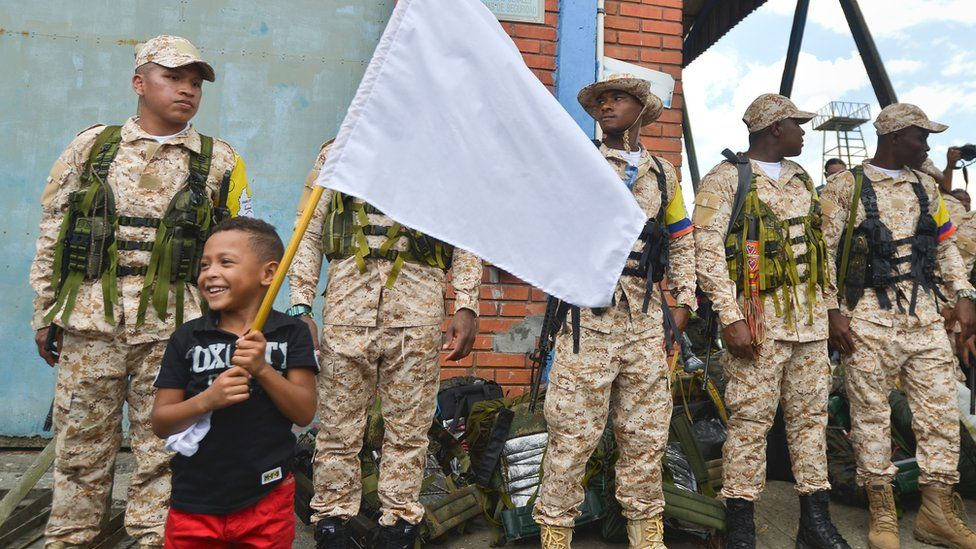A boy holds a white flag next to a group of members of the Farc guerrilla who arrived in Buenaventura, Colombia, on February 4, 2017
