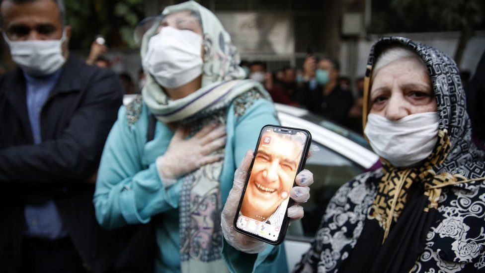 """Female fans of Iran""""s legendary singer, instrumentalist, and composer Mohammad-Reza Shajarian, holding pictures of him, as they mourn in front of the Jam hospital, where Shajarian reportedly passed away, in Tehran, Iran, 08 October 2020."""