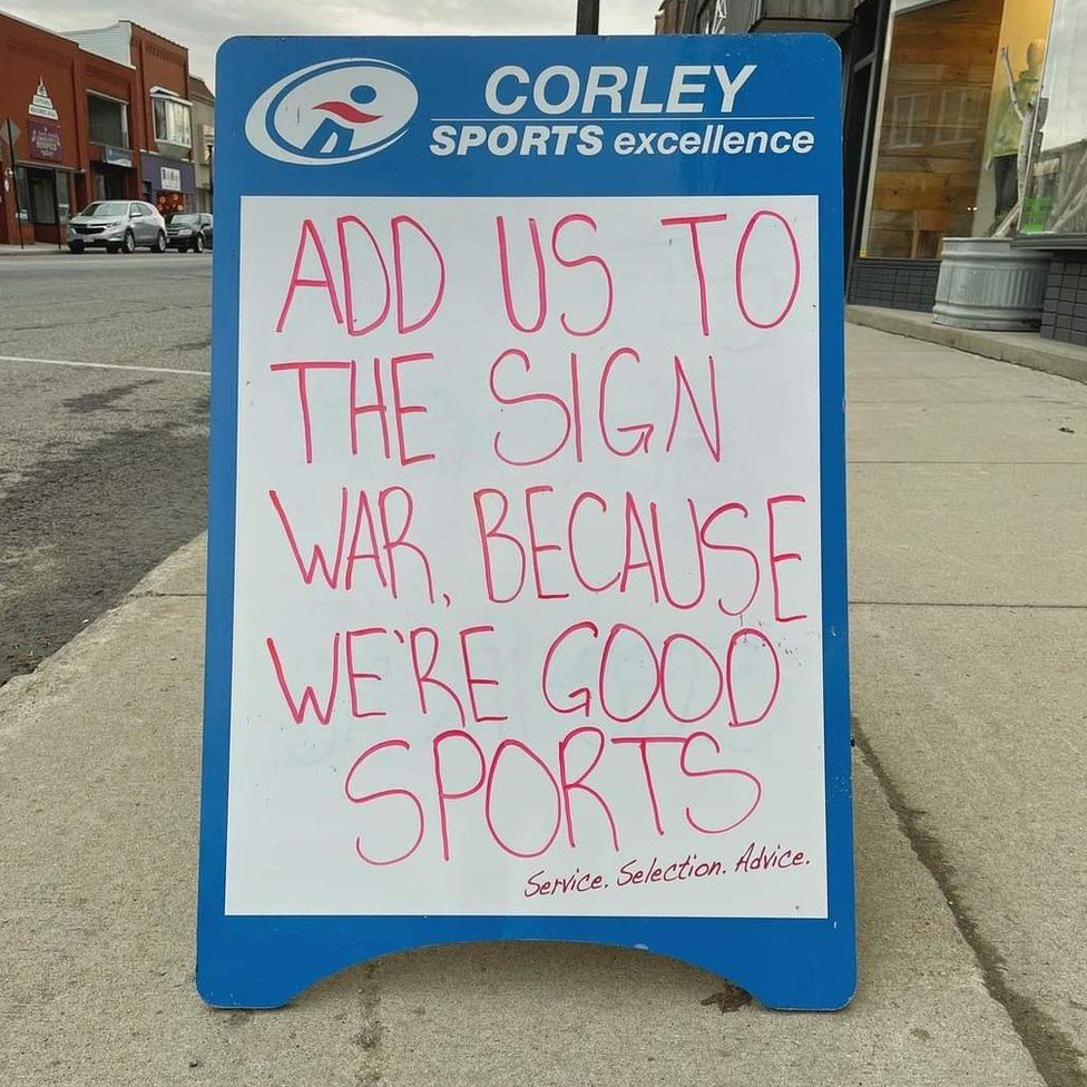A sign from a sports shop reads 'add us to the sign war because we're good sports'