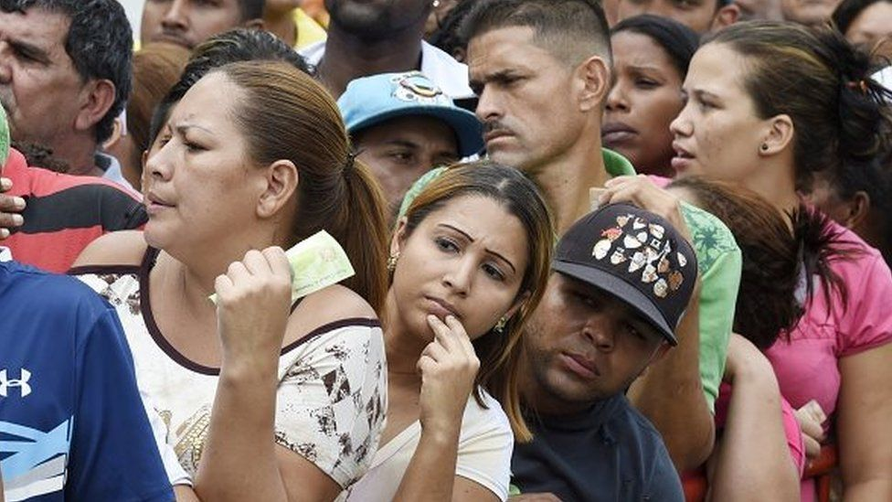 People queue to buy chicken behind a fence at a street market in Caracas on 24 January, 2015