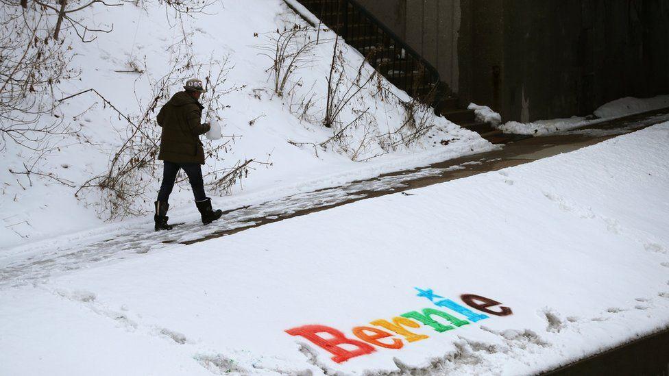 A man walks past a sign in the snow for Democratic 2020 U.S. presidential candidate and U.S. Senator Bernie Sanders in Ames, Iowa, U.S., January 25, 2020