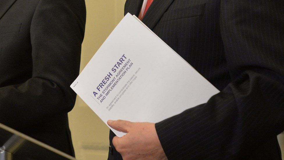 First Minister Peter Robinson holds a copy of A Fresh Start: The Stormont Agreement and Implementation Plan