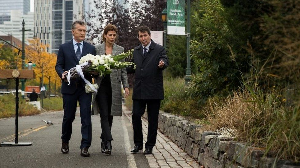 Argentinian President Mauricio Macri and First Lady of Argentina Juliana Awada carry flowers as they attend a tribute for the victims of last week's vehicular attack, November 6, 2017 in New York City.