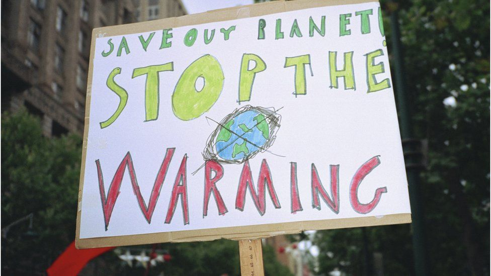 Close-up of global warming sign in city