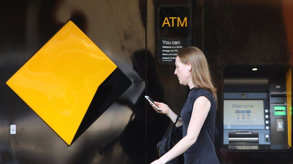 A woman walks past a Commonwealth Bank of Australia branch