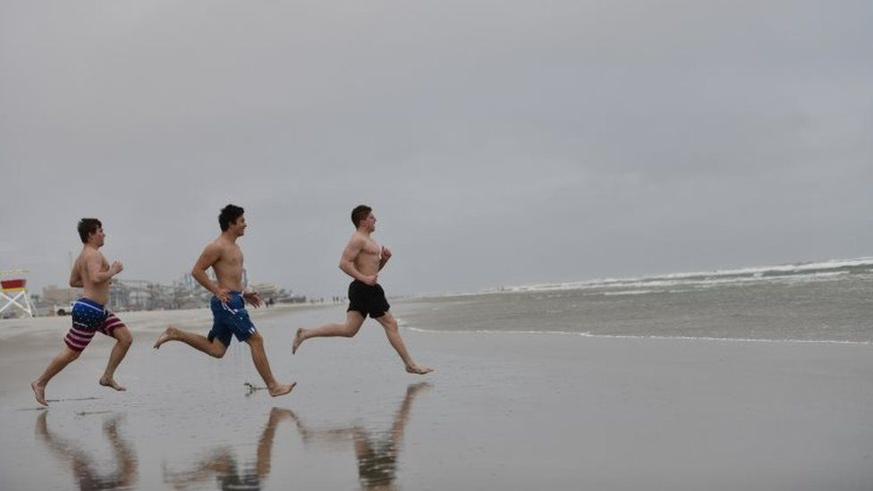Teenagers race into the ocean on a cold day at the beach in Wildwood, New Jersey. Photo: 24 May 2020