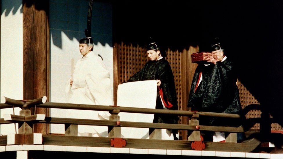 Emperor Akihito accompanied by Shinto priests carrying an Imperial Treasure  at the palace (1990)