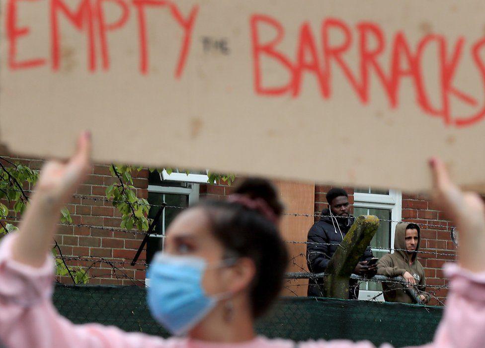 Asylum seekers watch a protest outside Napier Barracks