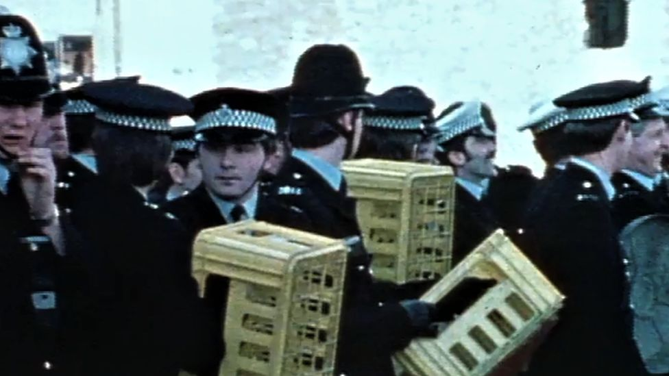 Police officers defend themselves with milk crates