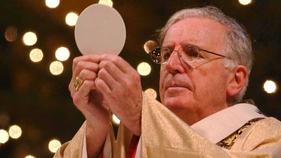 The Cardinal holds up a communion wafer