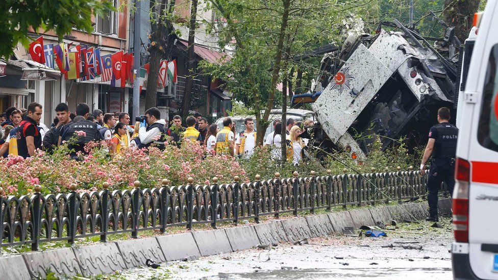 People stand beside beside a Turkish police bus which was targeted in a bomb attack in a central Istanbul