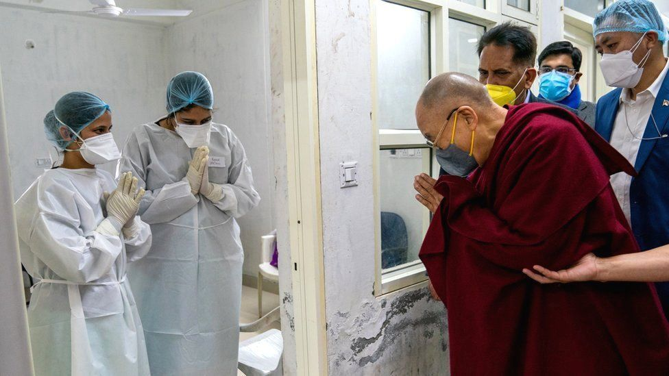 Tibetan spiritual leader the Dalai Lama (R) greets the medical staff after receiving a Covid-19 vaccine in Dharmsala, India, 6 March 2021