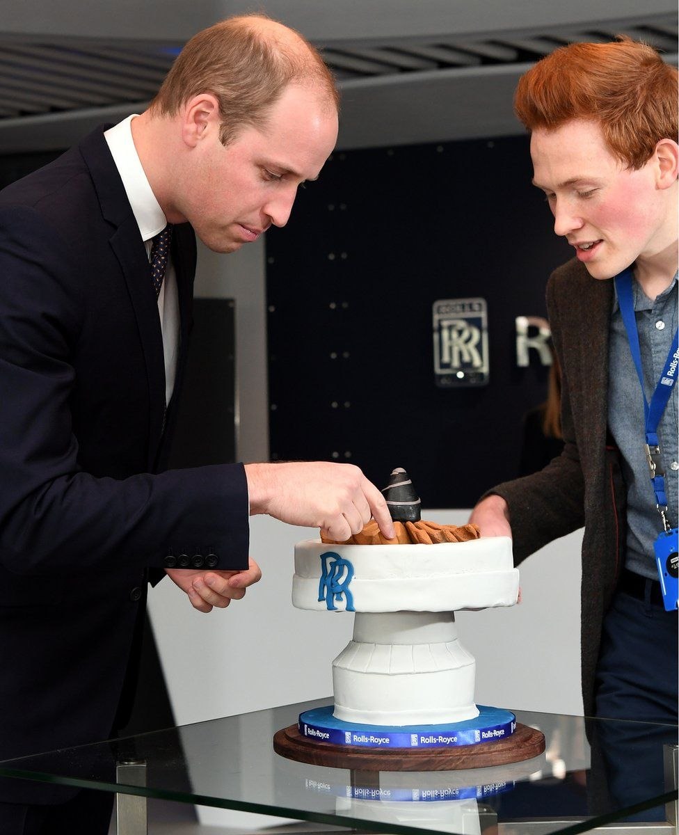 Prince William, Duke of Cambridge is presented with a cake by aerospace engineer and Bake Off runner-up Andrew Smyth during a visit to the Rolls-Royce technology centre on November 30, 2016 in Derby
