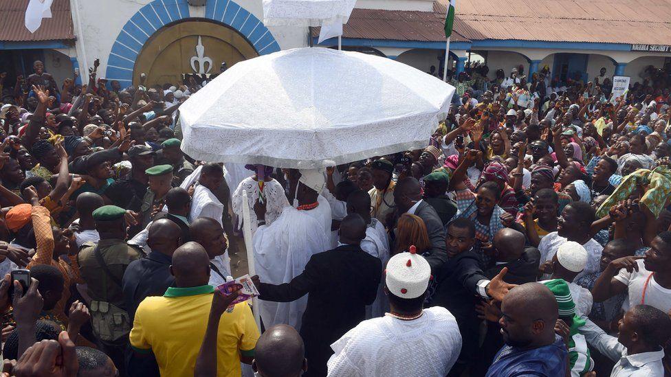 Adeyeye Enitan Ogunwusi under an umbrella