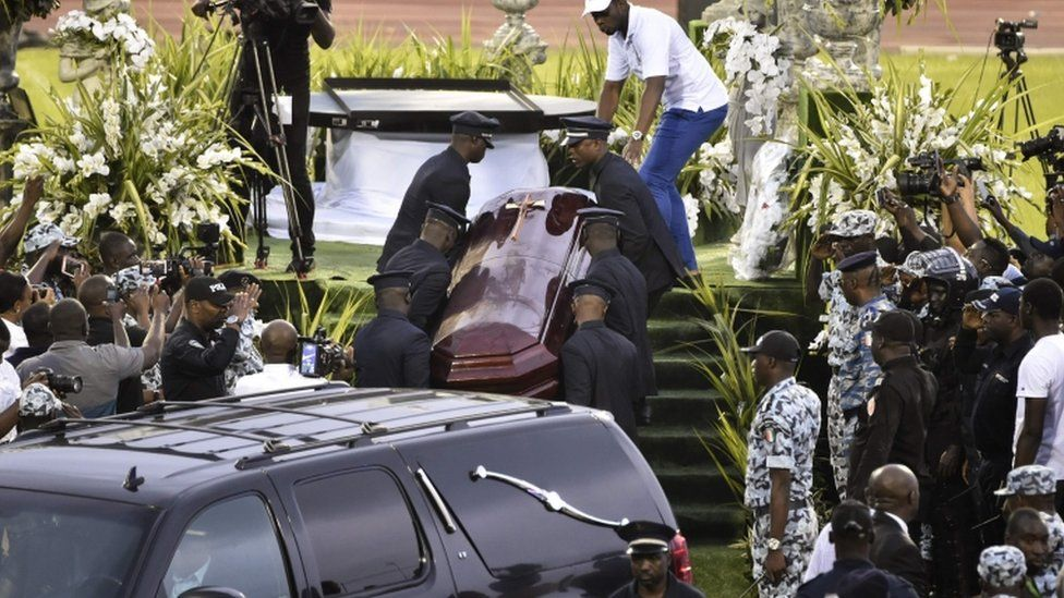 Pallbearers carry the coffin of late Ivorian singer DJ Arafat leaves the Felix Houphouet-Boigny stadium in Abidjan