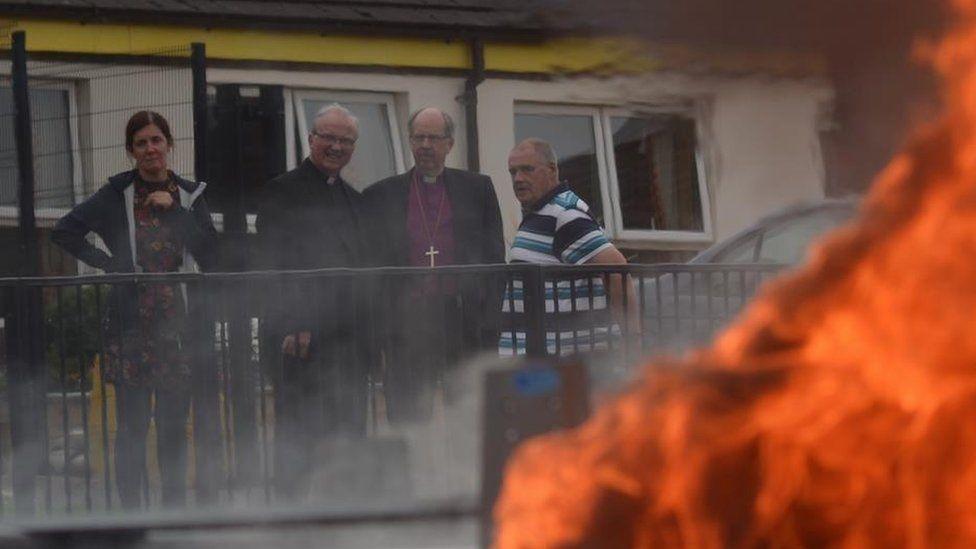 Bishops looking at van on fire.