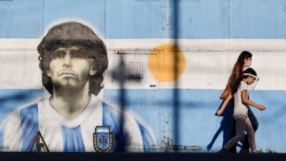 Two people walk past a mural of Maradona