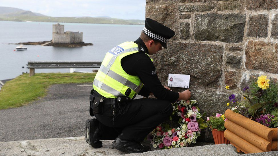 Police officer lays floral tribute from Manchester at the church on Barra