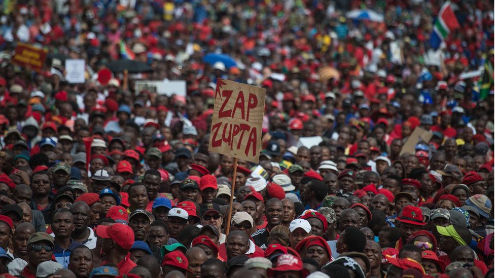 "A protester holds a placard reading ""Zap Zupta"", refering to Zuma and the Gupta Family, as South African demonstrators from various political and civil society groups march through the capital Pretoria calling for President Jacob Zuma to resign on April 12, 2017."