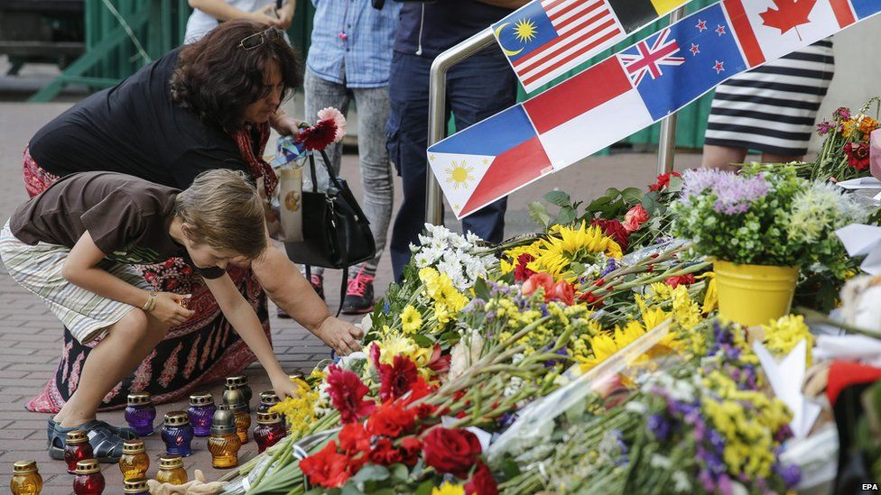 A woman and a young boy place flowers in commemoration of the victims of Malaysia Airlines MH17 plane accident in eastern Ukraine