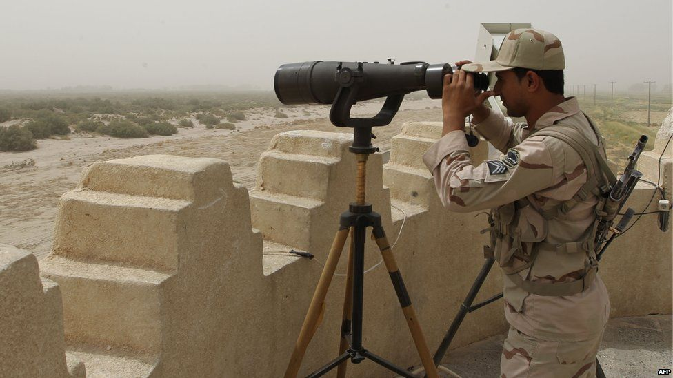 Iranian border guard looks through binoculars (file photo)