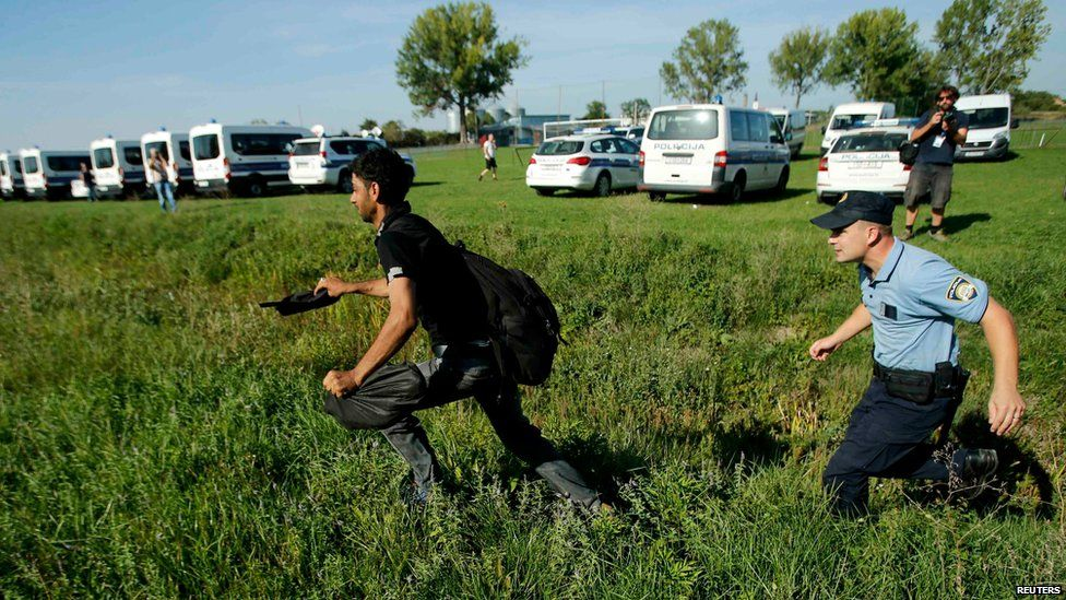 A migrant and a policeman run during a stampede to board a bus in Tovarnik, Croatia (September 17, 2015)